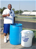 Coach Parker poses with recycling bins to support the Recycling at Port Allen High School program