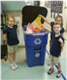 Three children recycling construction paper