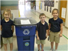 Three children pose next to recycling container
