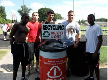 Guys pose with Recycle Cans and Bottles sign
